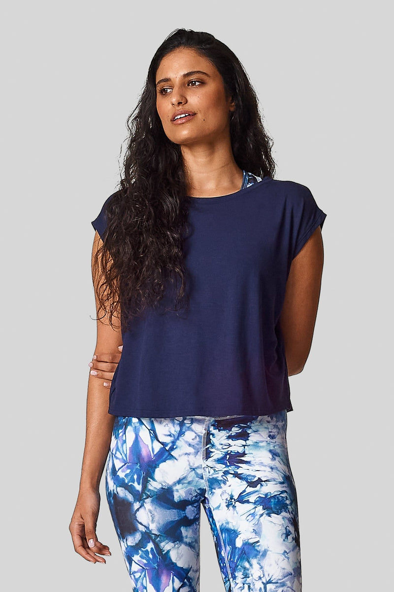A brunette is wearing  a navy marine box tee with an exclusive printed legging.
