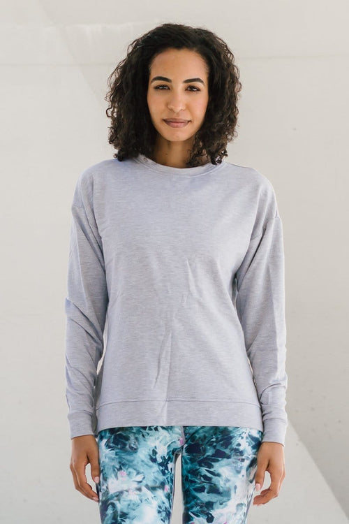 Woman with dark curly hair wearing long sleeve crewneck sweater made in Canada ethical basic in Heather Grey.