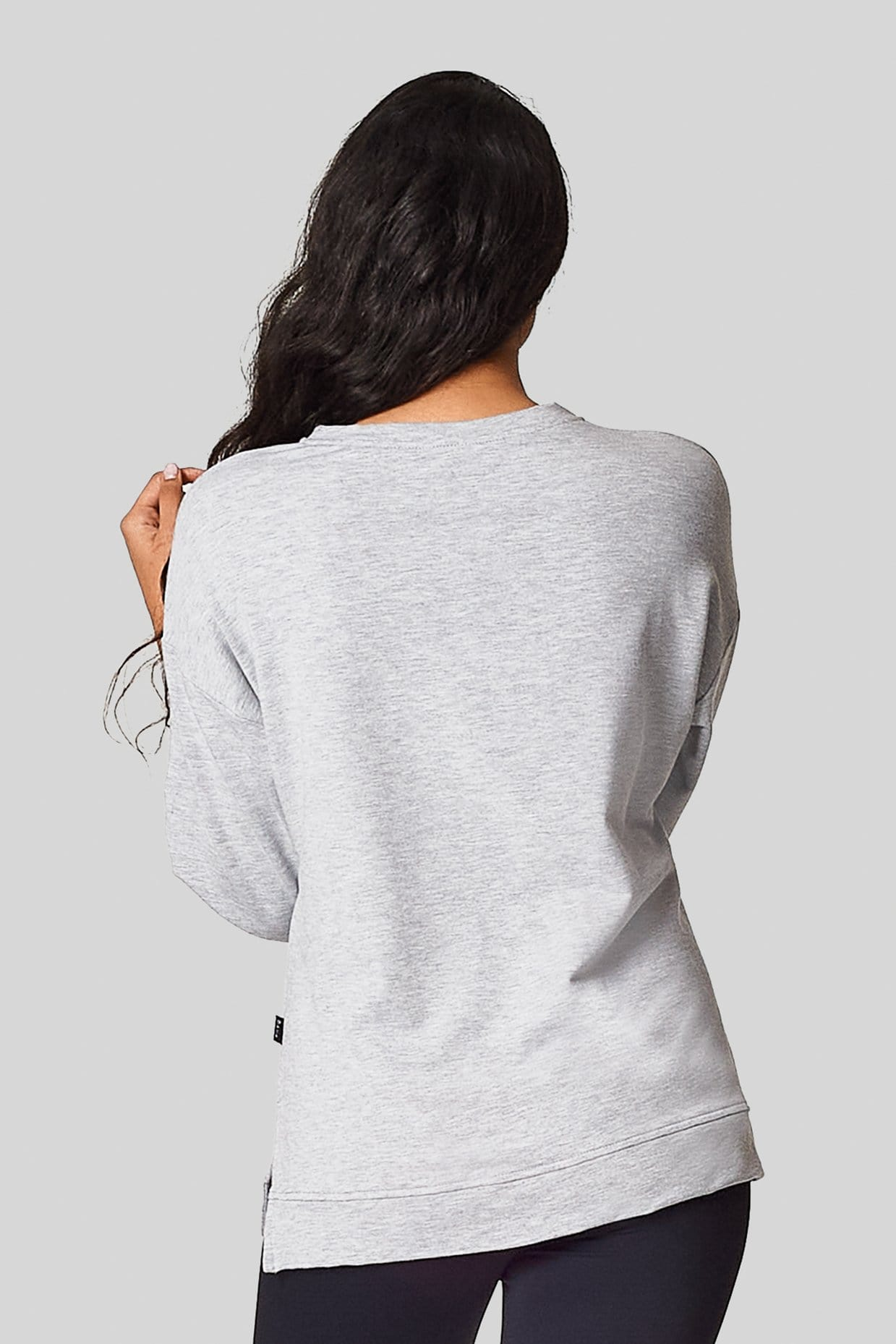 The back view of a brunette wearing a light heather gray sweatshirt with side slit.
