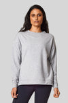 A dark haired woman wears a light heather grey sweatshirt made from bamboo fleece.