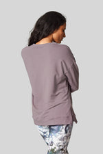 Back view of a woman wearing a cozy light grey crewneck sweatshirt with dropped shoulder. Worn with tie dye leggings.
