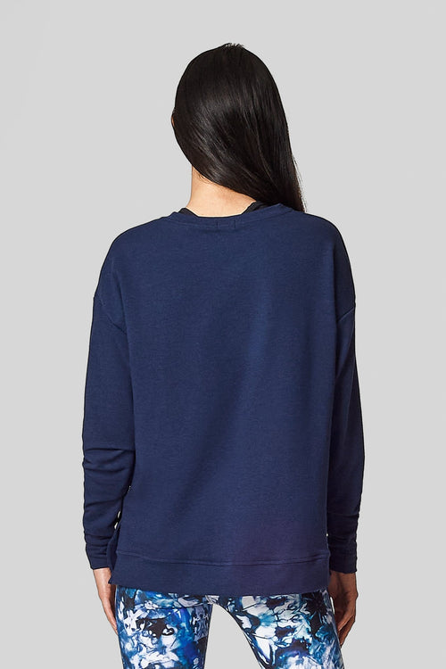 The back view of a black haired woman wearing a navy sweatshirt and blue tie-dye leggings.