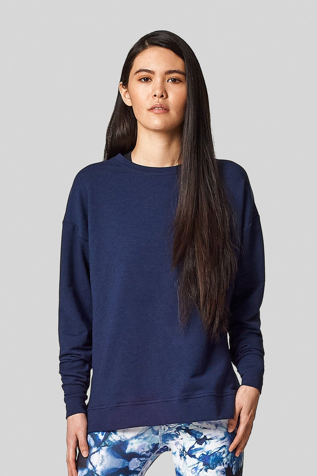 An asian woman wears a navy blue crewneck sweatshirt.