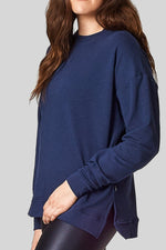 A woman wears a navy sweatshirt with crewneck and side slits.