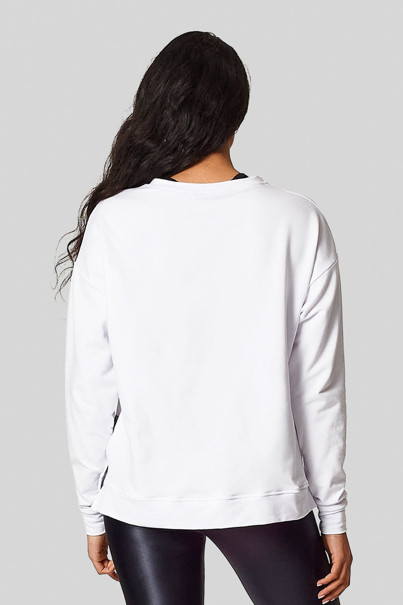 The back view of a woman wearing a white long sleeve sweatshirt. Bamboo fleece and made in Canada.