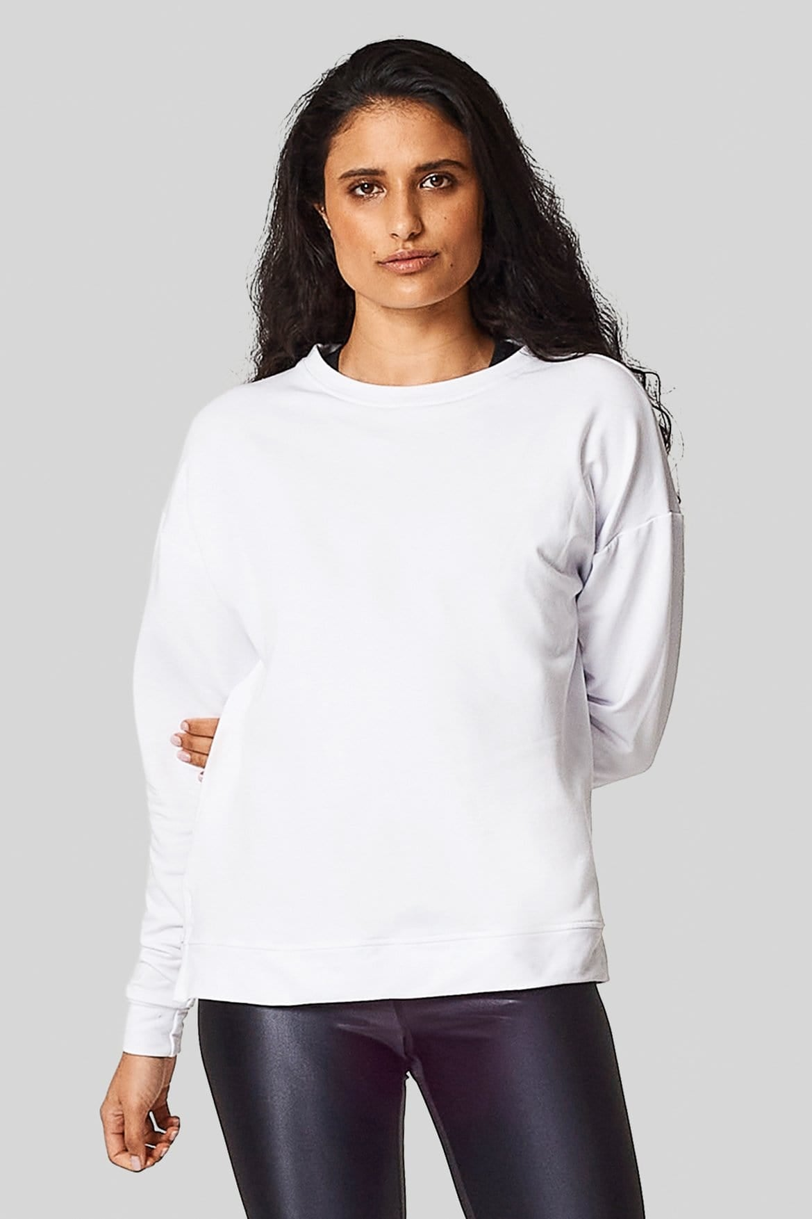 A woman wears a white crewneck sweatshirt made of bamboo fleece with black liquid leggings.