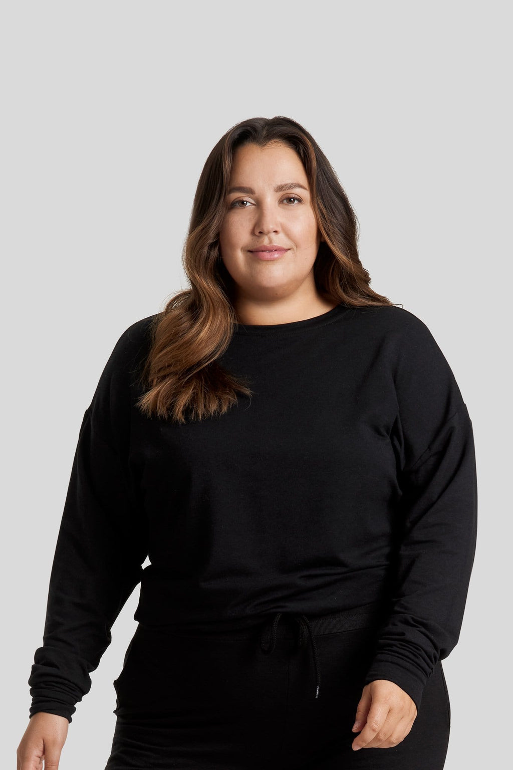 A woman wearing a black crewneck sweater