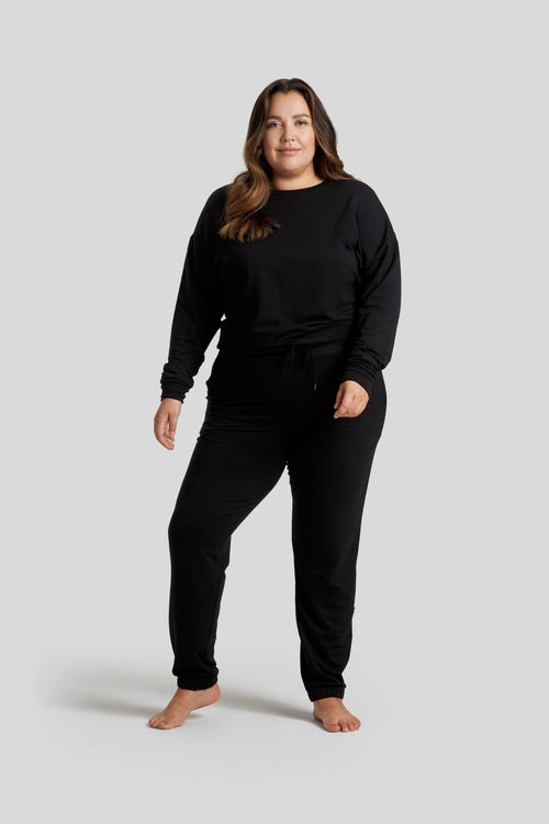 A woman is shown wearing a black crewneck longsleeve sweater and black sweatpants