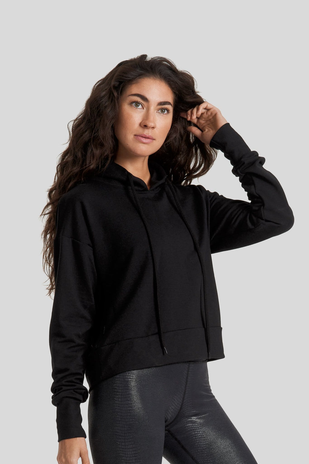 A woman wearing an all black hoodie and shiny textured leggings
