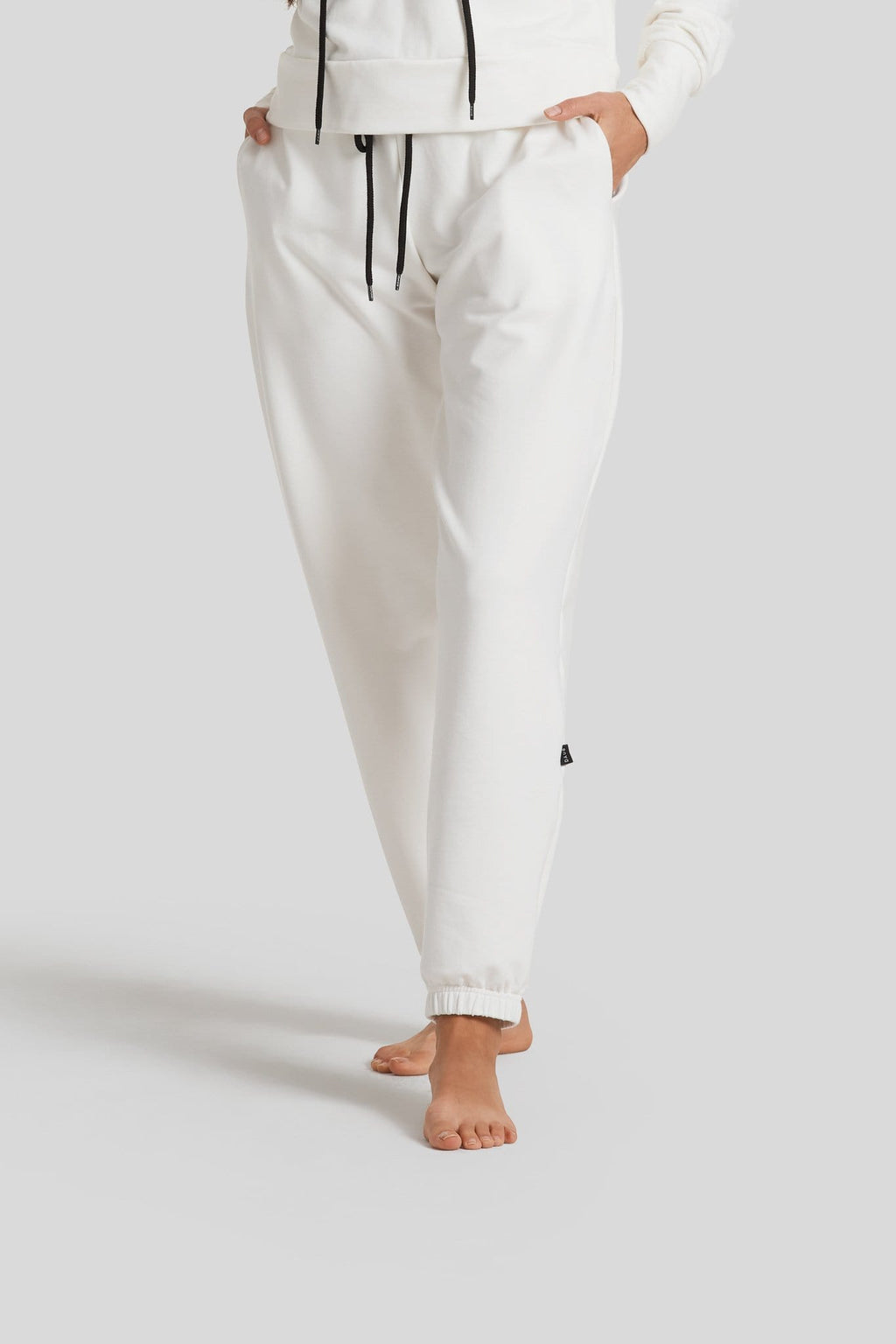 A woman's legs are shown wearing ivory colored sweatpants with a black drawstring