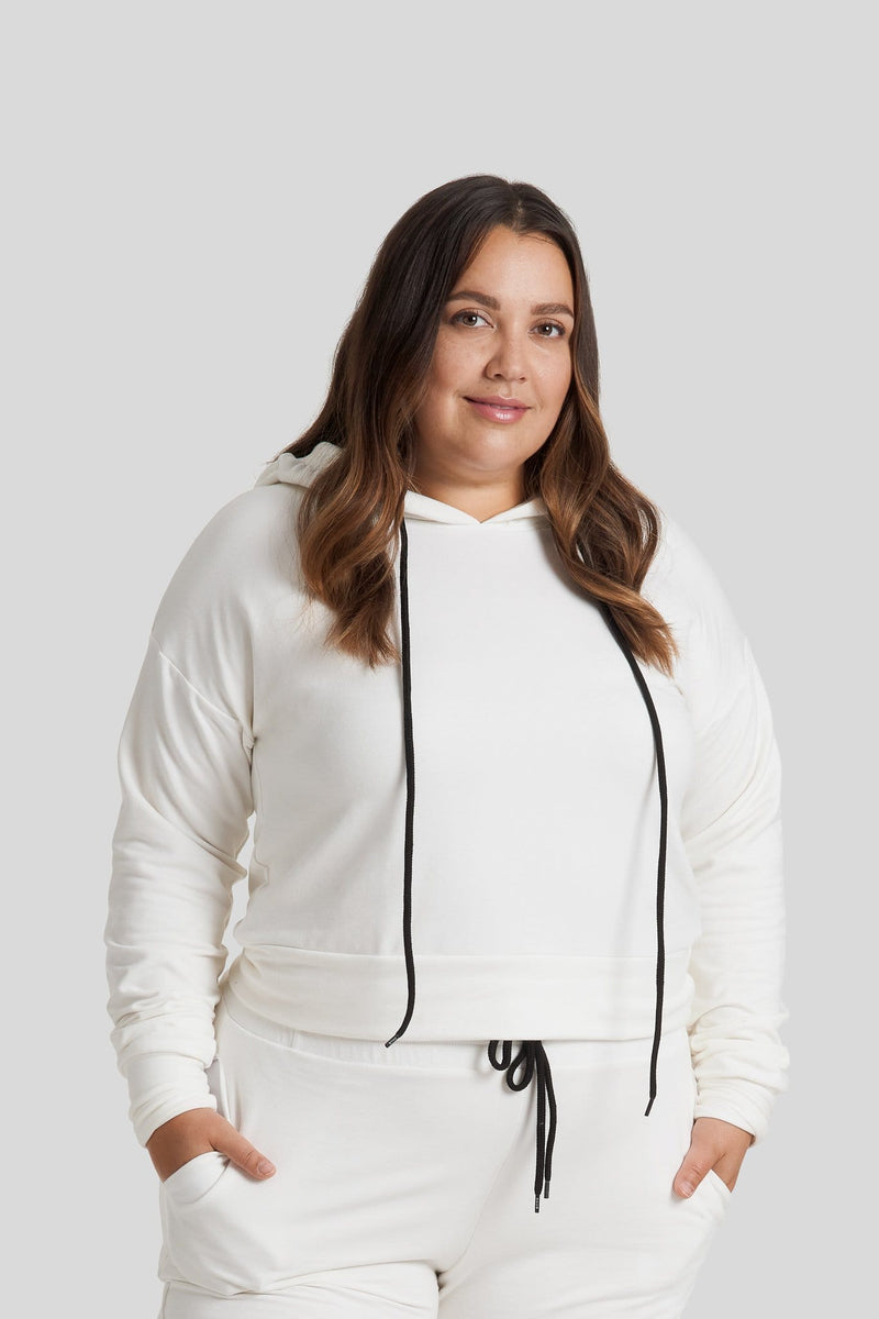 A woman wearing an ivory colored hoodie with matching ivory joggers