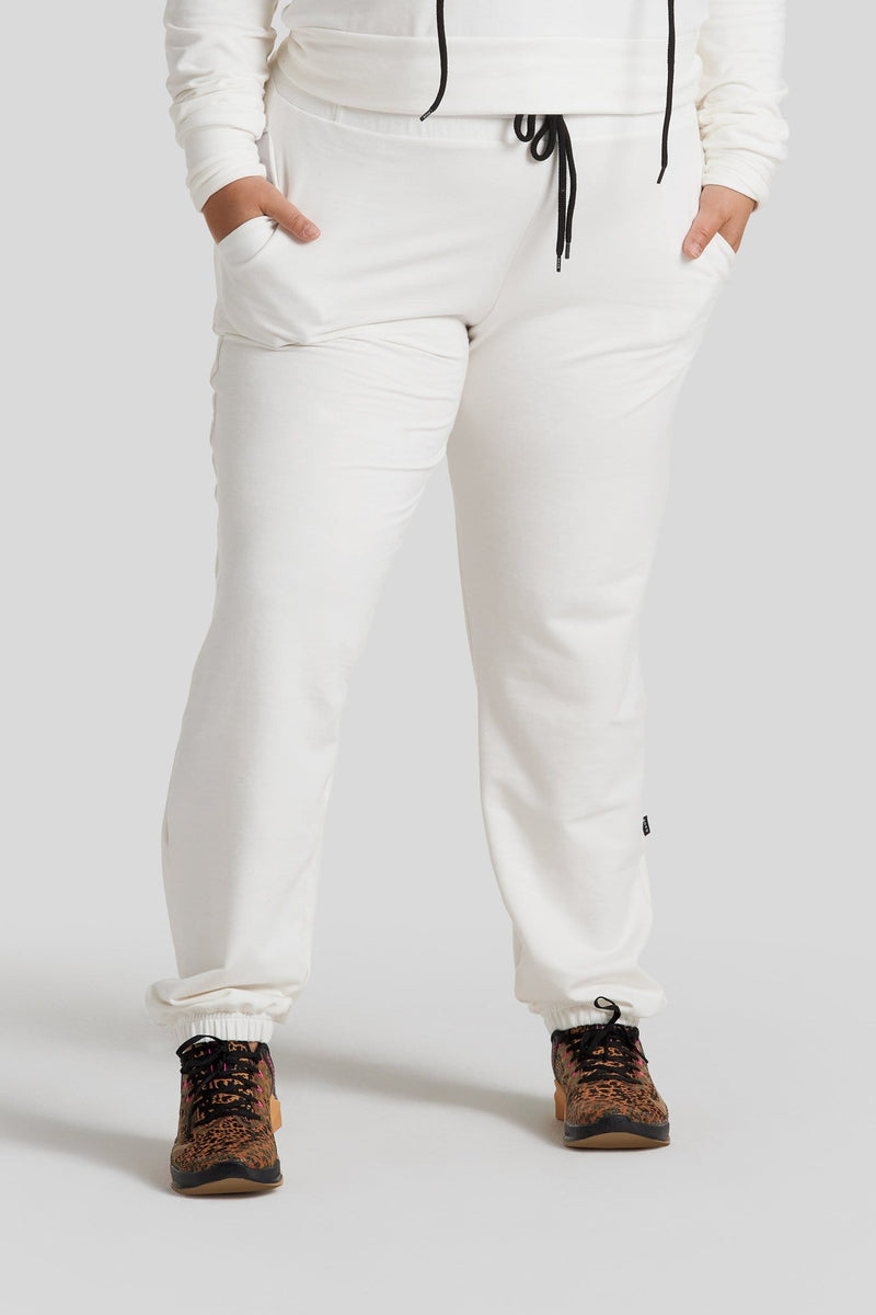 A woman's legs are shown wearing off-white colored sweatpants