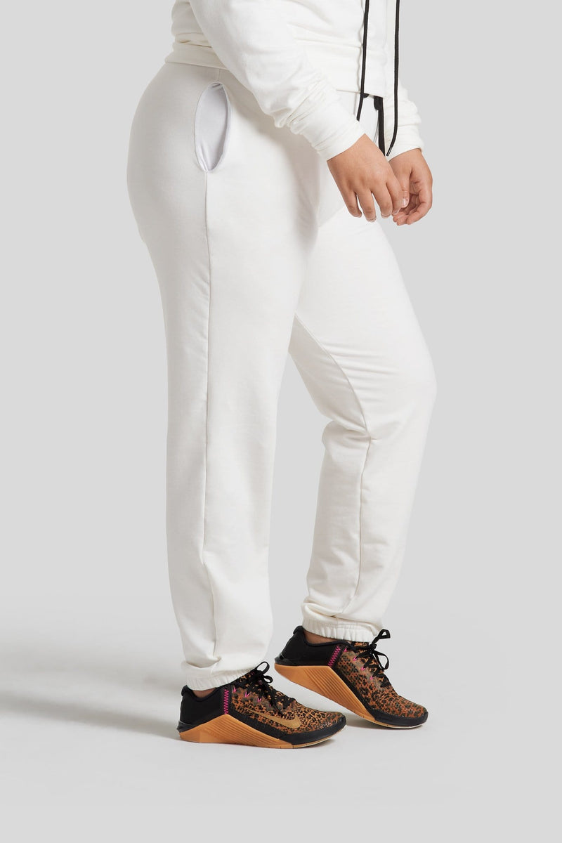 The side profile of a woman's legs are shown wearing ivory colored sweatpants