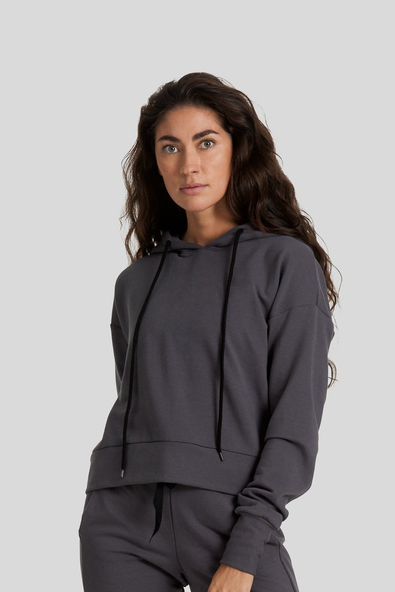 A brunette is shown wearing a graphite coloured fleece hoodie