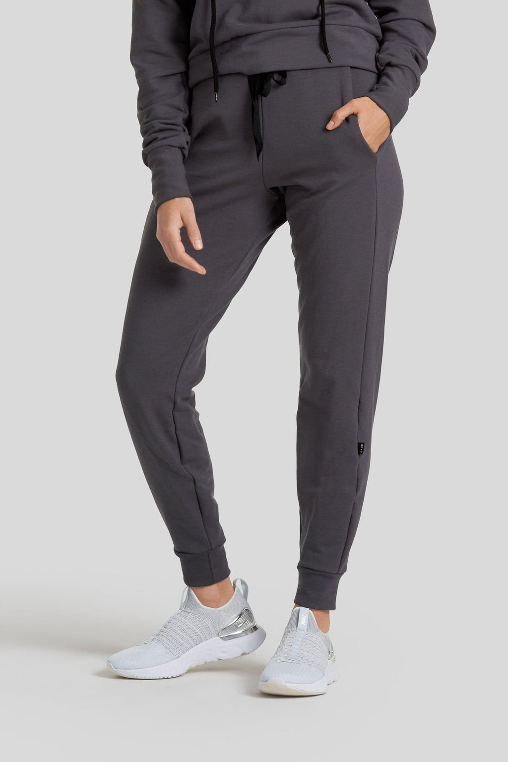 A woman's legs are shown wearing dark grey joggers