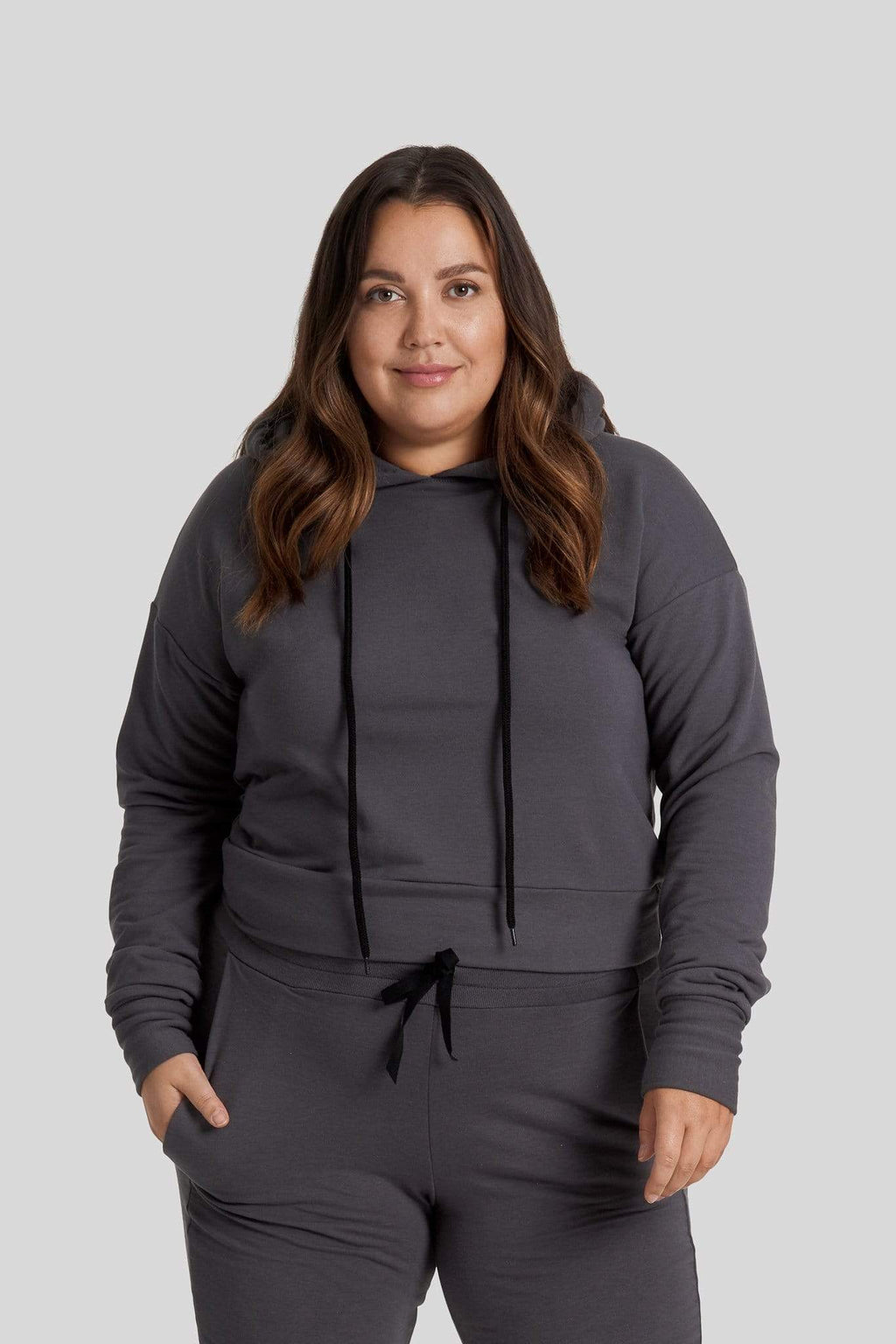 A woman is shown wearing a dark grey hoodie with matching joggers