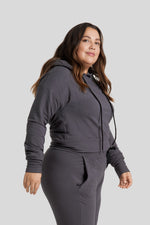 The side profile of a woman is seen wearing a graphite coloured hoodie and matching joggers