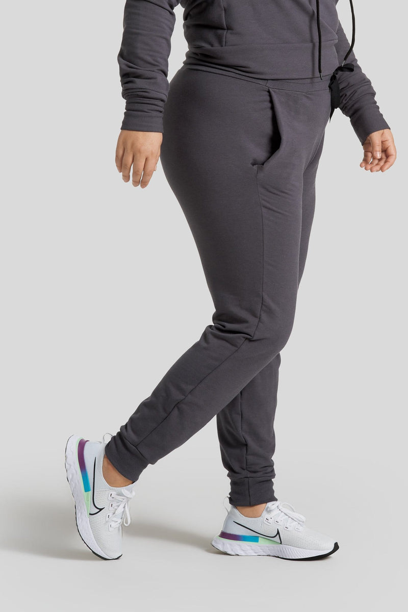 The side profile of a woman's legs are shown wearing graphite colored joggers