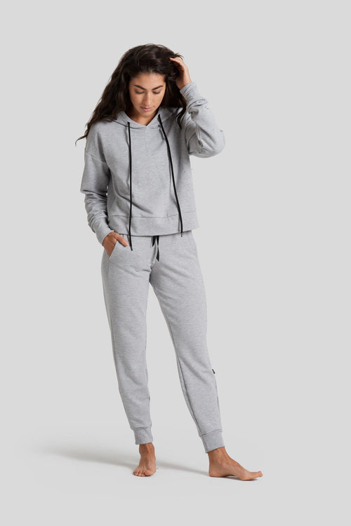 A woman is shown wearing a light grey hoodie with matching grey joggers