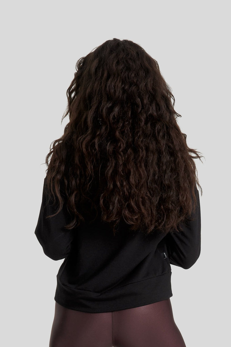 The back of a woman is shown wearing a black hoodie