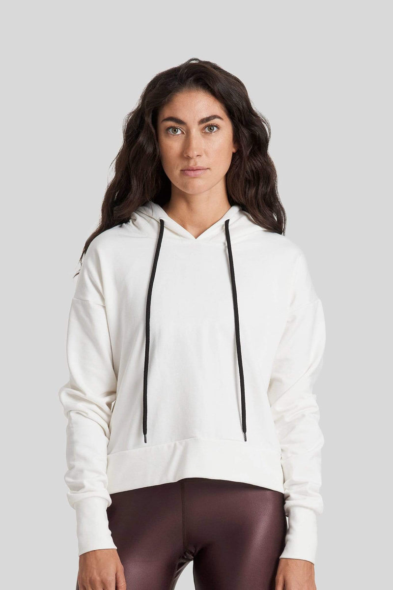 A brunette woman is seen wearing an off white hoodie and brown high gloss leggings