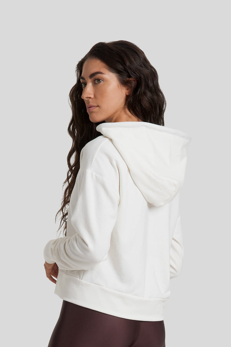 The back of a woman is shown wearing a ivory coloured hoodie