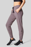 A woman stands with her hands in the pockets of her light taupe sweatpants.