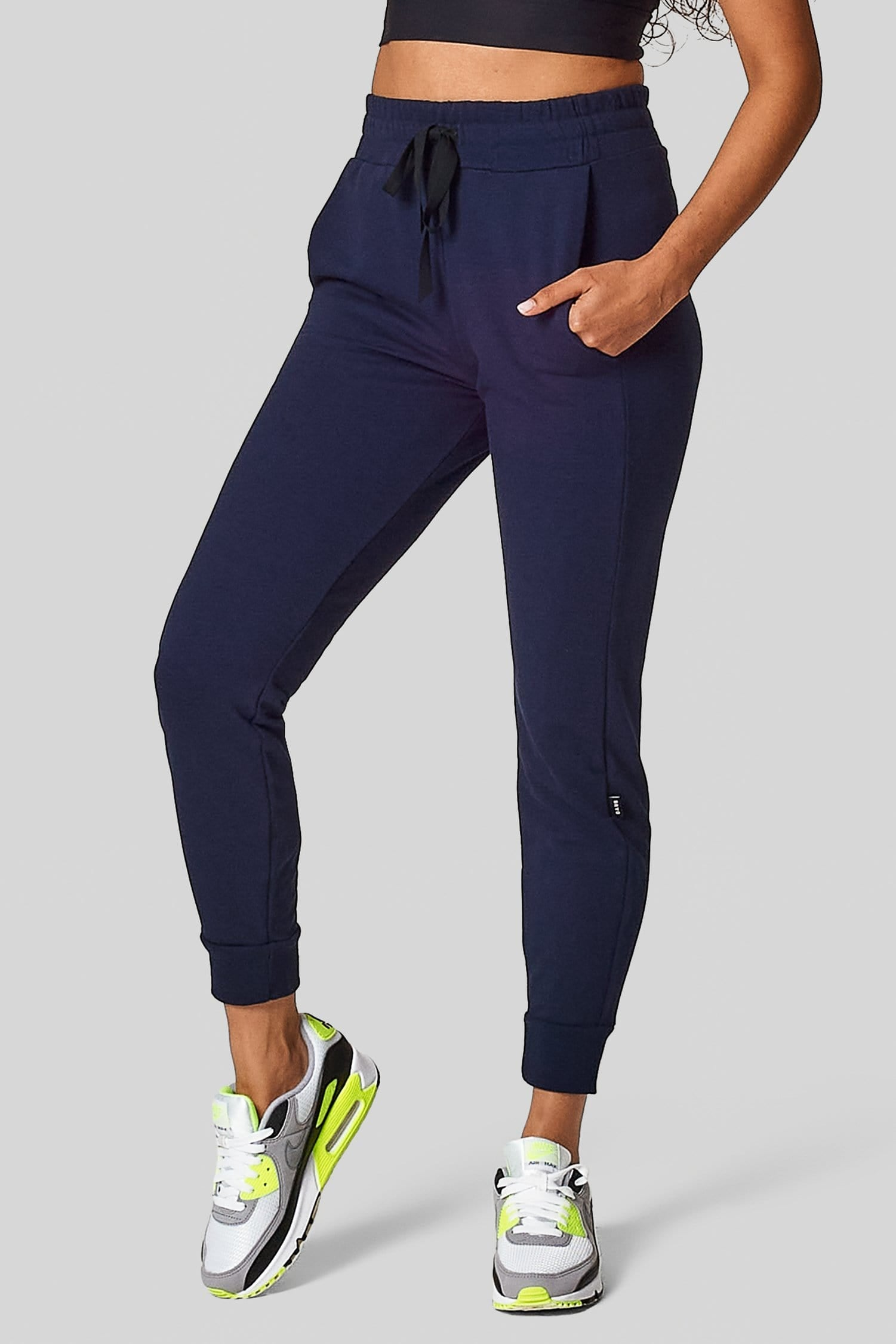 A woman wears a navy jogging pant with pockets and a drawstring.
