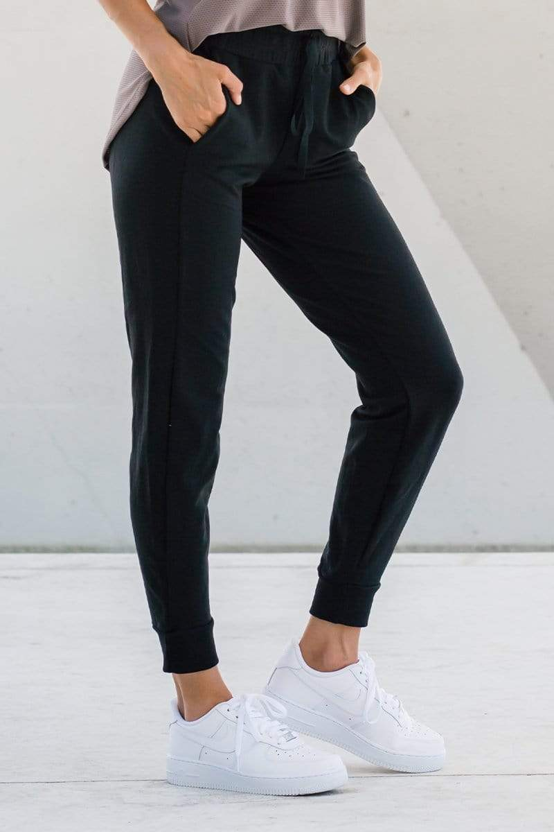 Side view woman wearing dressy jogger lounge pants in black made ethically in Canada with sustainable fabrics, sustainable jogger sweatpants available online in Canada.