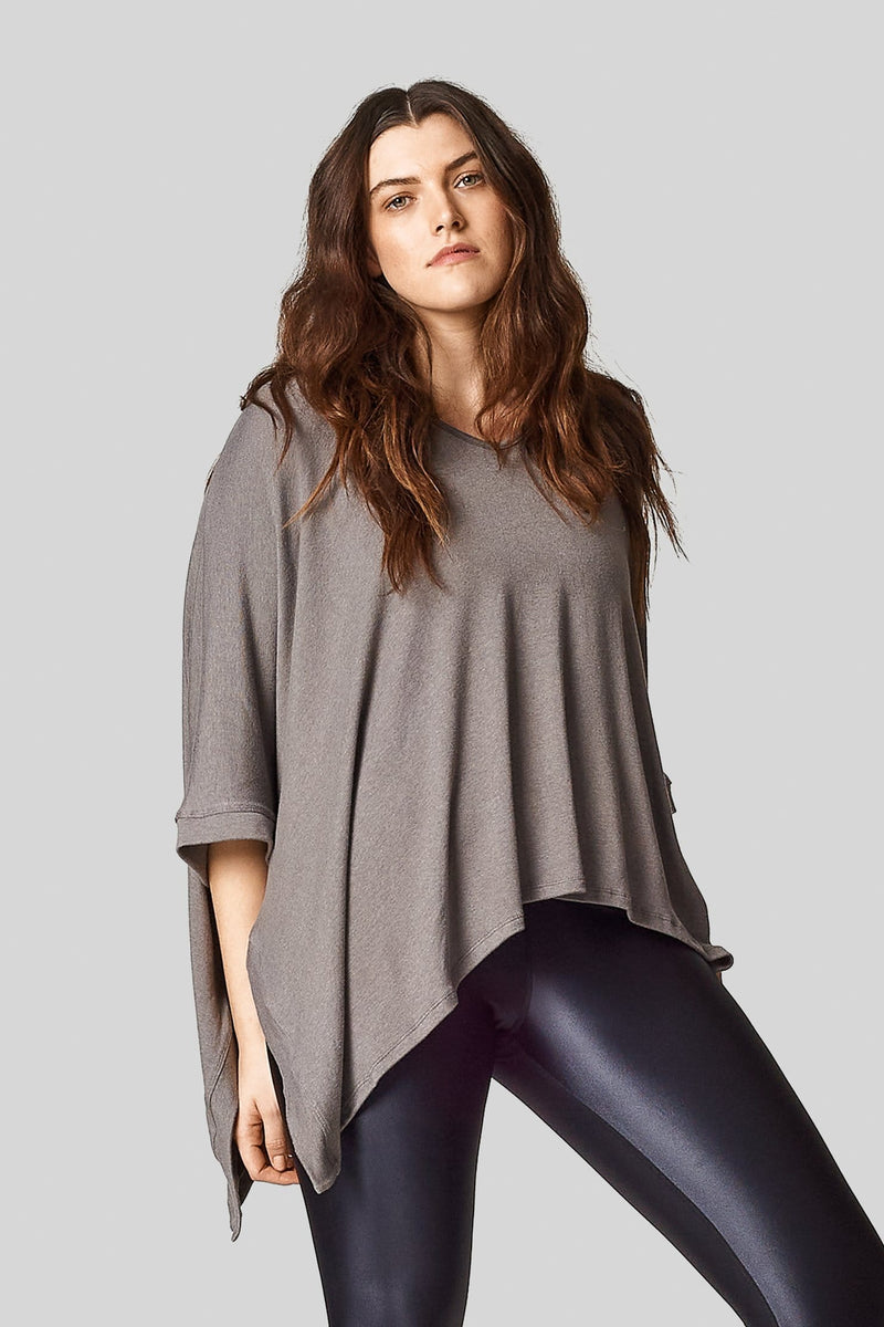 A brunette wears a light grey sweater knit poncho and black liquid leggings.
