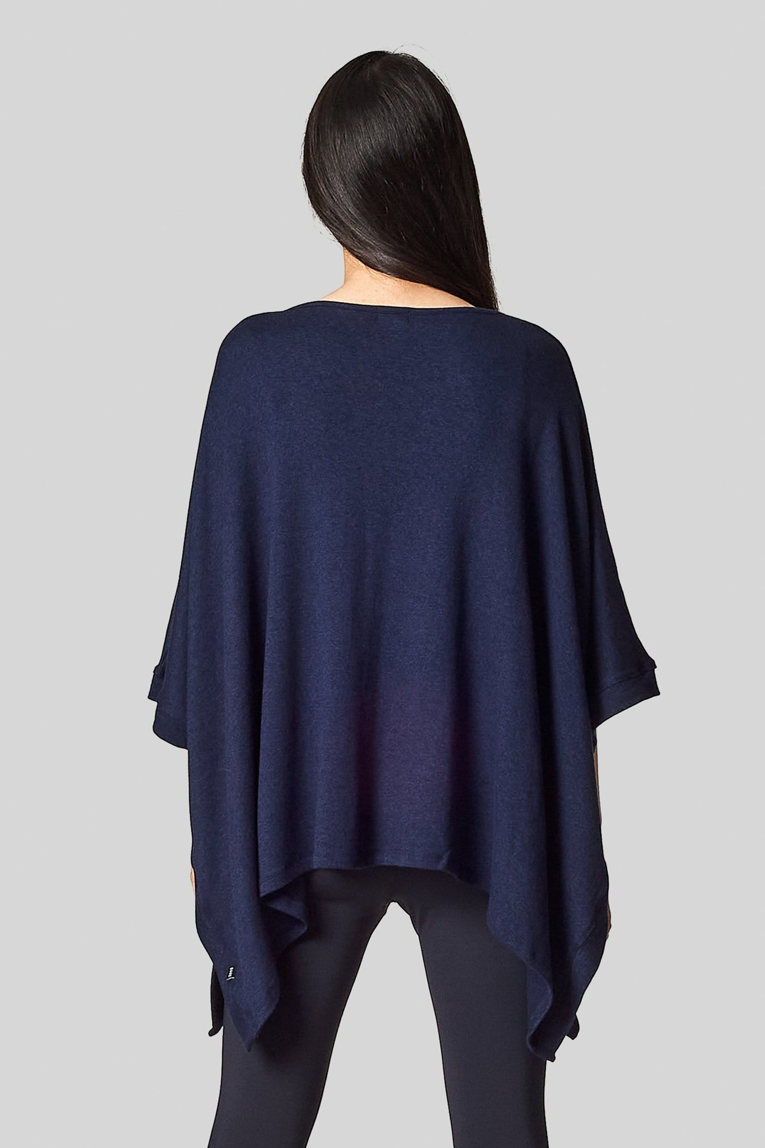 The back view of a woman wearing a navy blue poncho.