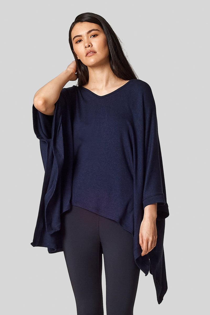 An asian female wears a blue v-neck poncho.
