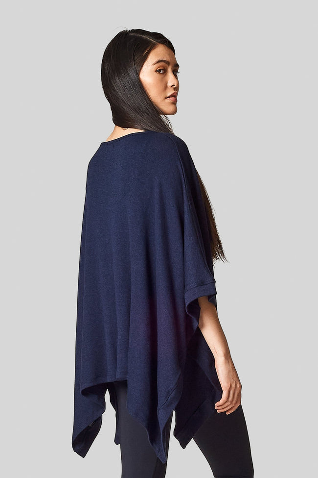 An asian model wears a navy blue poncho with black leggings.