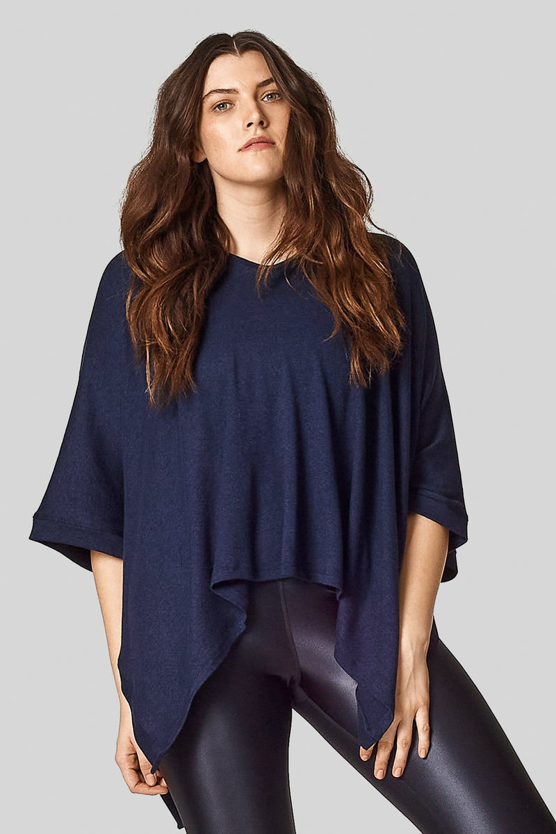 A brunette wears a navy blue poncho in a sweater knit with shiny black leggings.