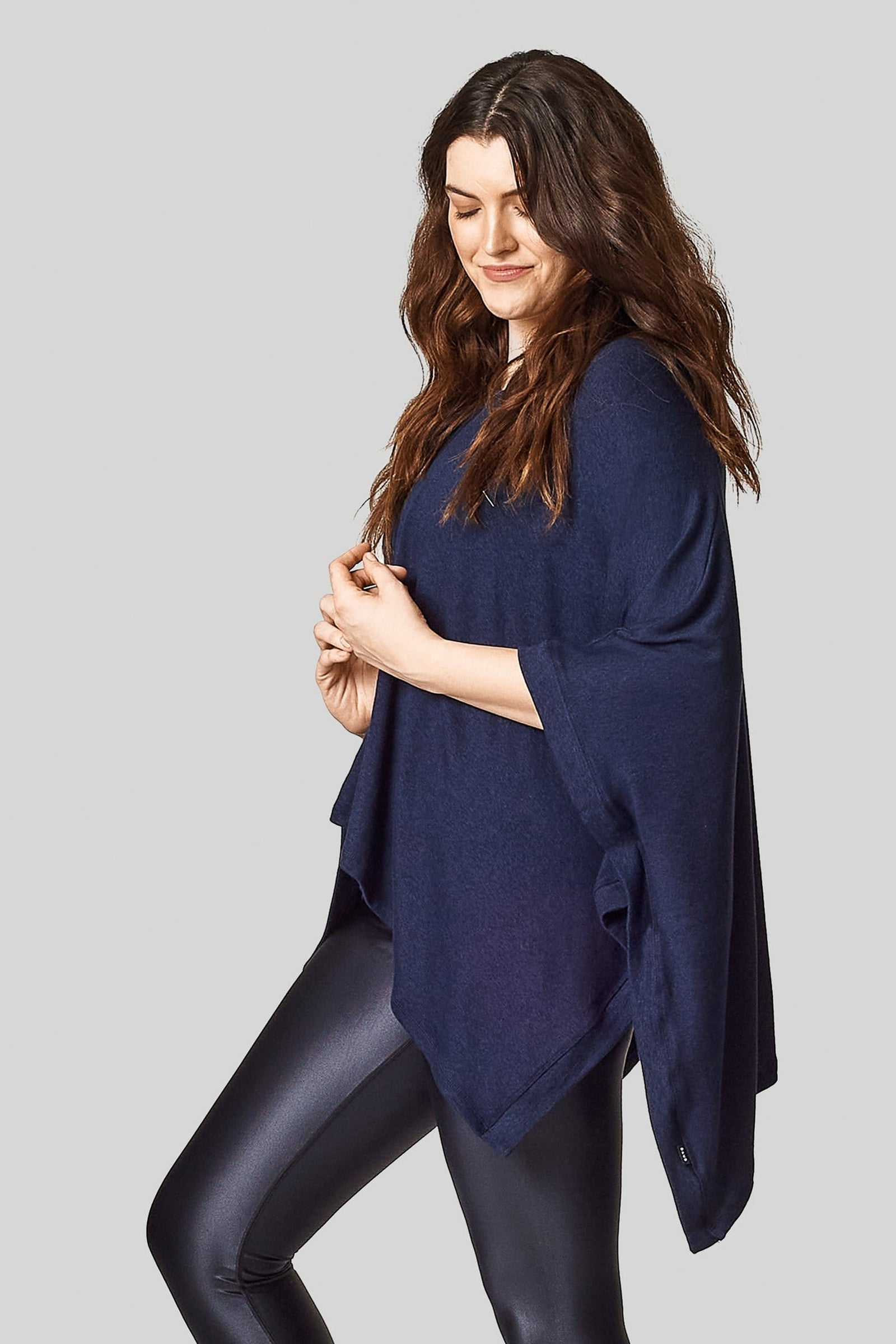 A side view of a caucasian brunette wearing a navy blue poncho.