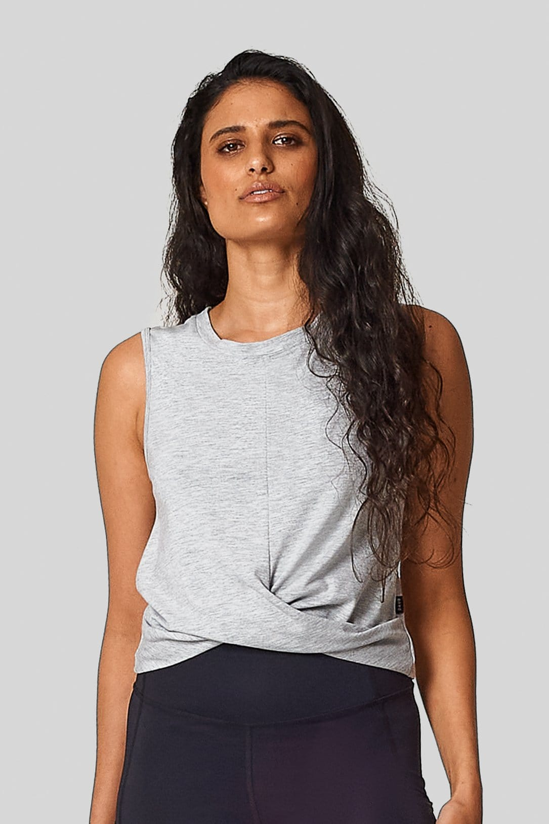A woman wears a sleeveless tank in light heather grey that crosses over at lower centre front. Worn with black pocket leggings.
