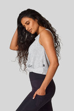 Side view of the Leilani tank - a sleeveless top with a front twist. Worn with a black pocket legging.