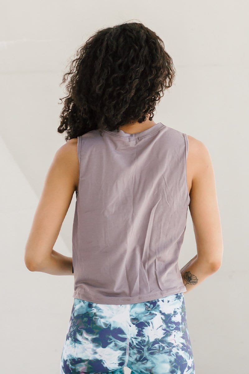 Woman with dark curly hair standing wearing beige made-in-Canada ethical tank cropped with a knot accent.
