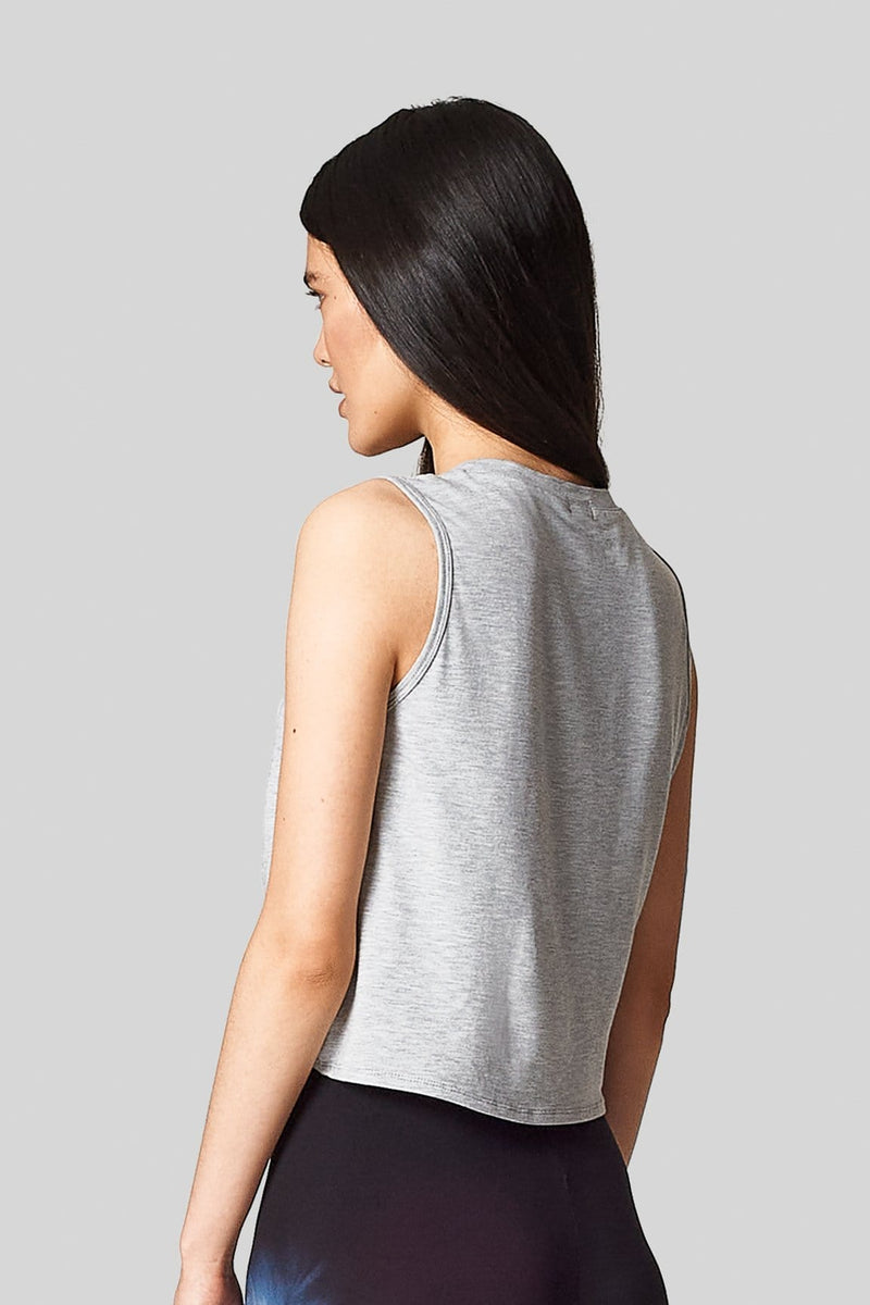 Back view of a woman wearing a sleeveless tee-shirt that is hip length in heather grey.