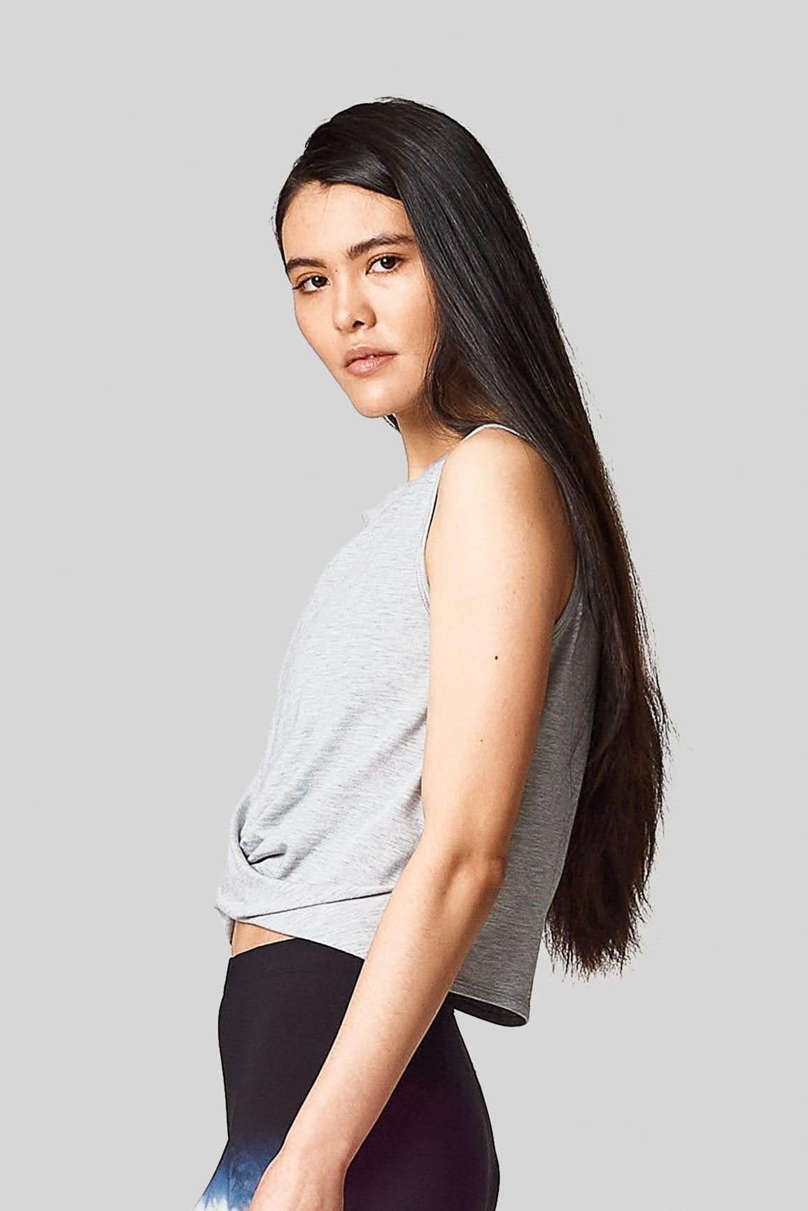 Side view of an asian model wearing a cropped sleeveless tee with a front twist.
