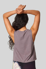 A woman stands with her arms above her head with a sleeveless tank in warm grey.