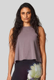 A brunette wears a neutral taupe colored sleeveless top with hand-dyed leggings.