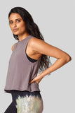 A brunette wears a taupe sleeveless tank for yoga.