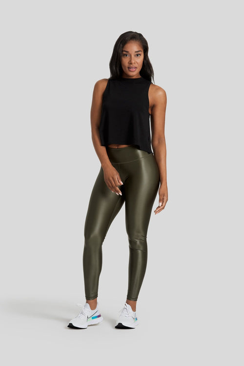 A woman is shown wearing dark green liquid leggings and a black sleeveless top