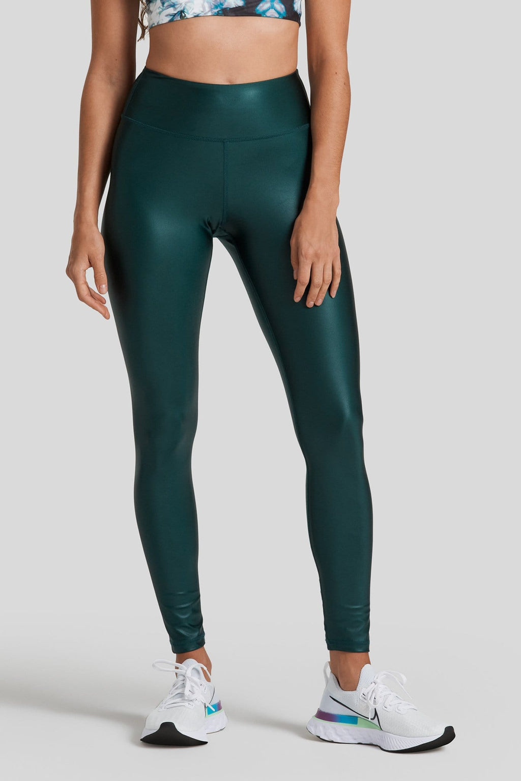 A woman is shown wearing dark green liquid leggings