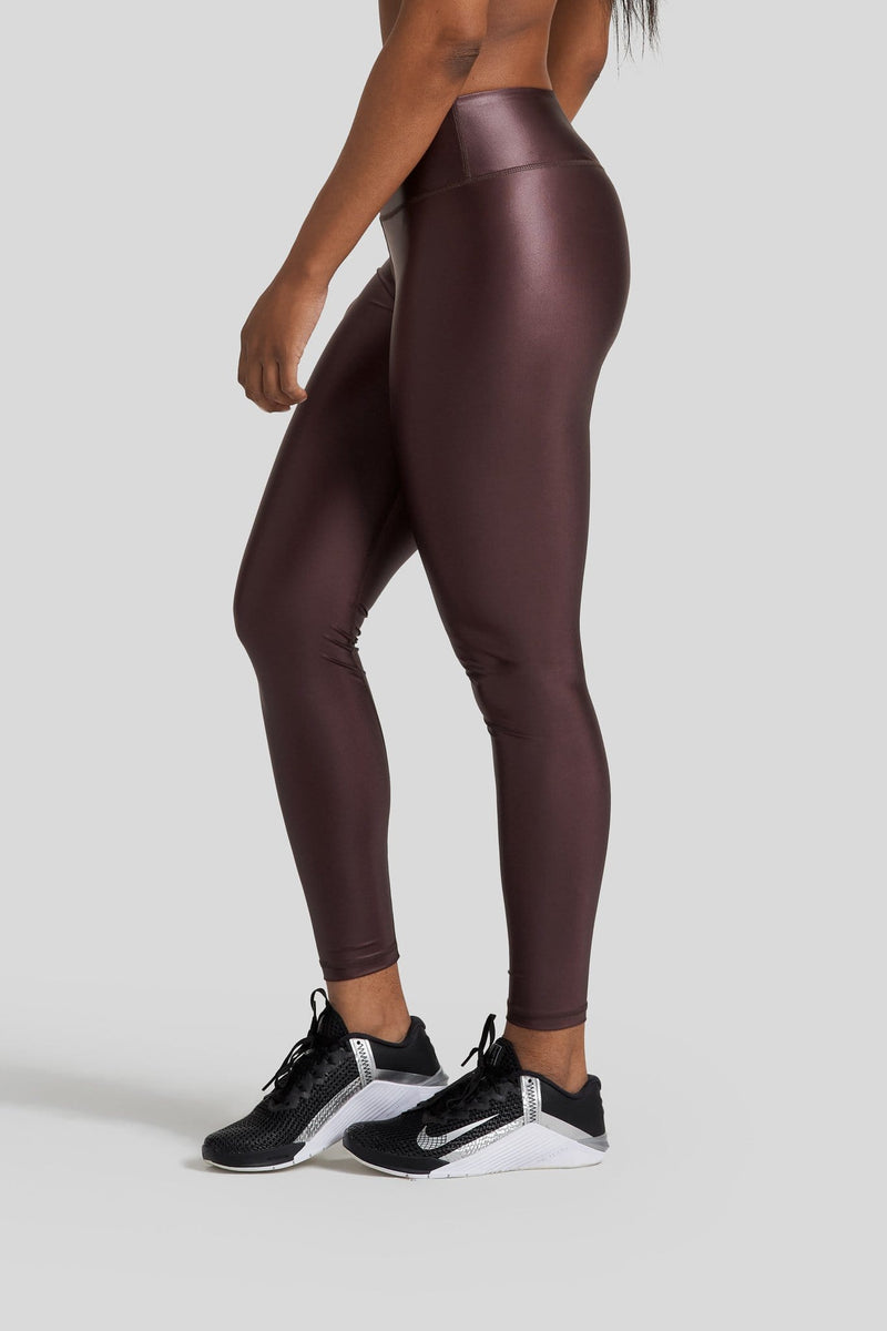 The side profile of a woman's legs are shown wearing hi gloss brown leggings