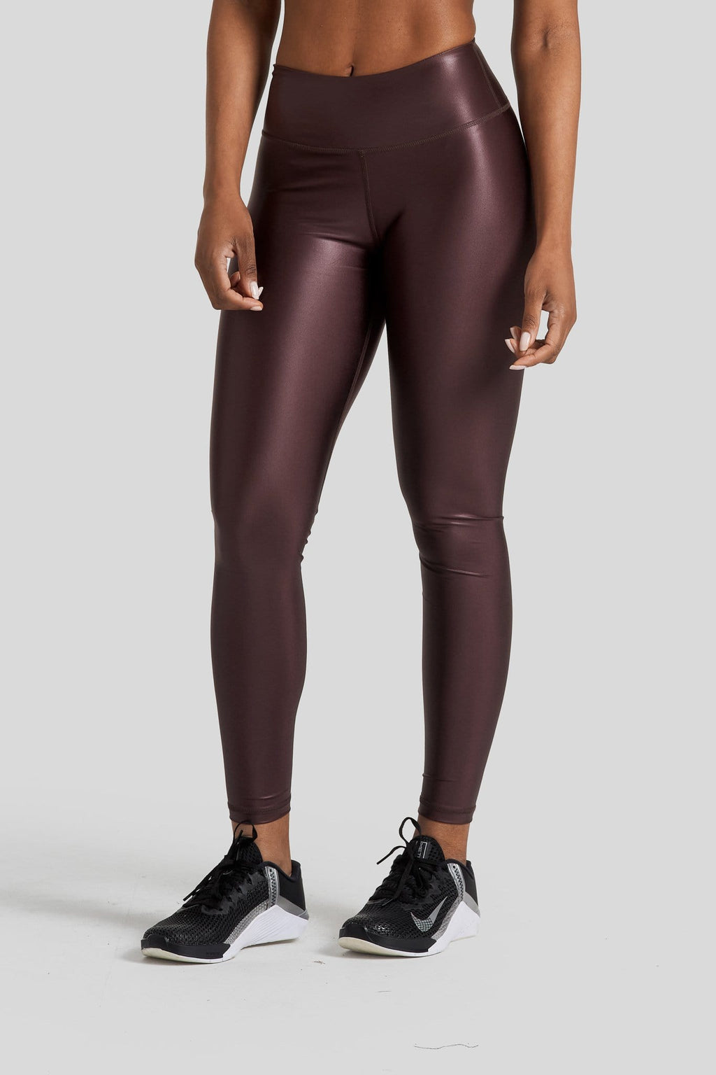 A woman's legs are shown wearing shiny brown leggings