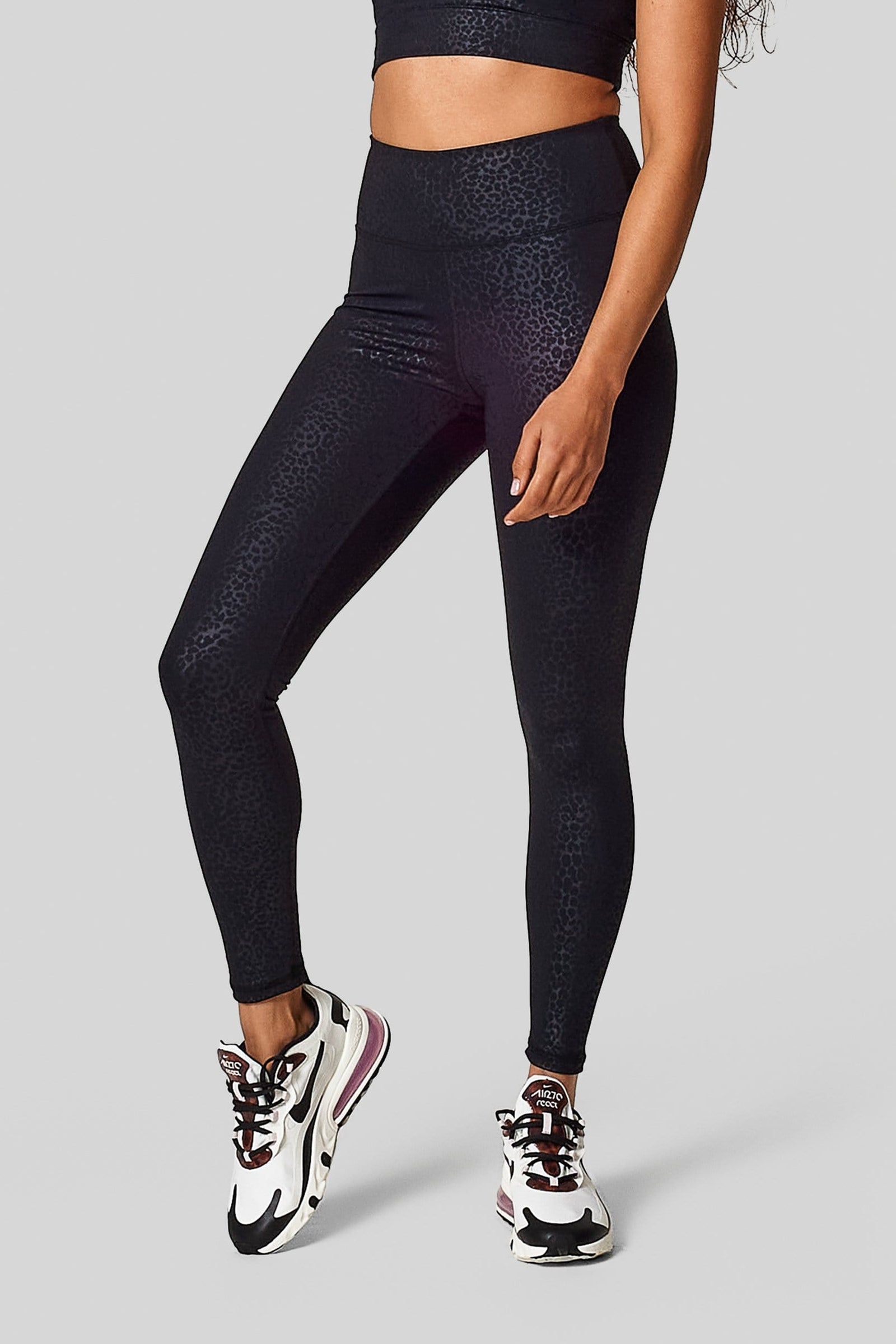 A woman wears new nikes with a pair of black Cheetah print high waisted leggings.