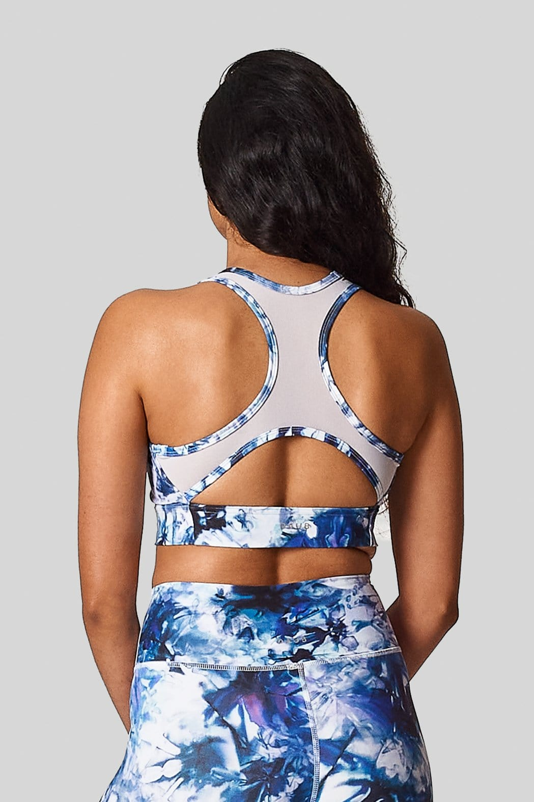 Back view of a tie dye blue mesh back long line sports bra.