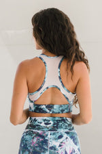 Woman wearing longline racerback sports bra with mesh detailing in blue and white tie-dye, ethically-made in Canada.